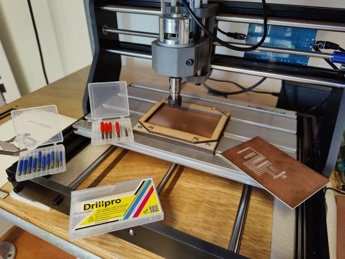 kleine CNC frees met een blanco printplaat ingespannen en een hoop freeskoppen in beeld
