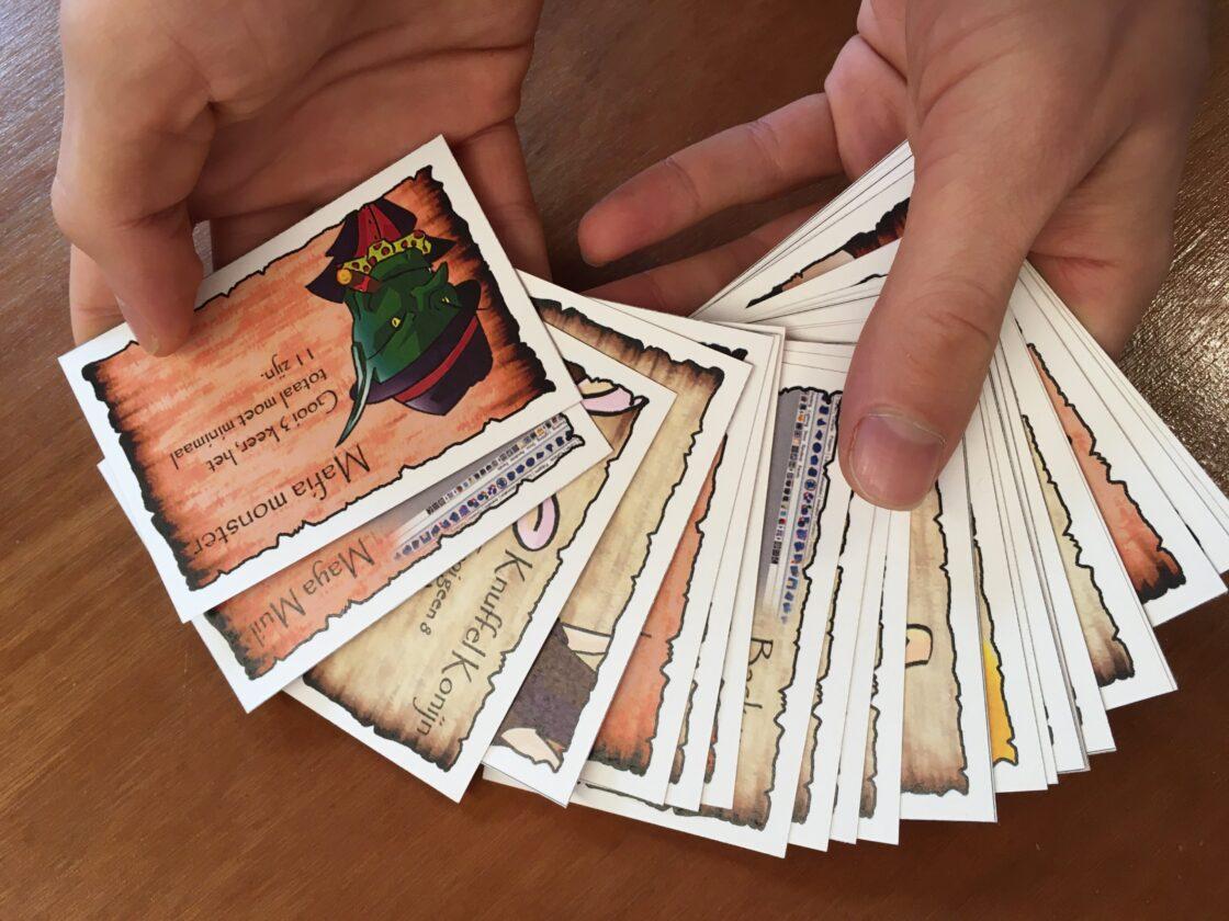 Twee handen met een waaier aan zelfontworpen speelkaarten
