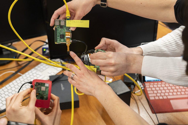 Vier paar handen met microcontrollers en kabels